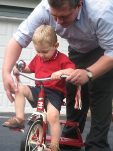 Boy learning to ride a tricycle