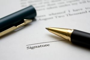 Pen resting on signature line