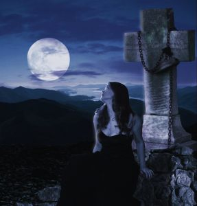 Paranormal/moody image of a woman in front of a stone cross in moonlight