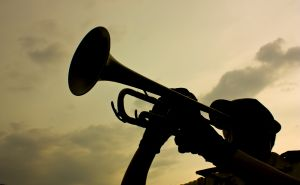 Silhouette of person doing a bugle call