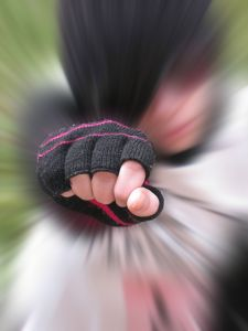 Blurred photograph of person punching toward viewer, only fist is in focus