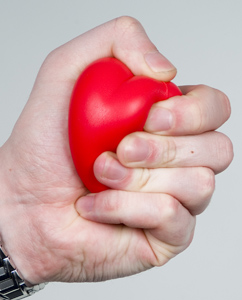 Tight hand squeezing a red foam heart