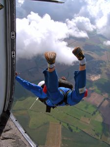 View from inside plane of a skydiver stepping out the door