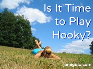 Woman lying down in a meadow with text: Is It Time to Play Hooky?