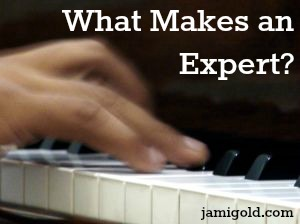 Fingers on a piano with text: What Makes an Expert?
