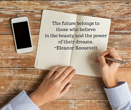 "Open notebook with quote: ""The future belongs to those who believe in the beauty and the power of their dreams. ~Eleanor Roosevelt"