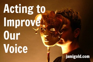 Actor holding up a mask with text: Acting to Improve Our Voice