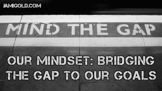 """Mind the Gap"" sign on pavement with text: Our Mindset: Bridging the Gap to Our Goals"