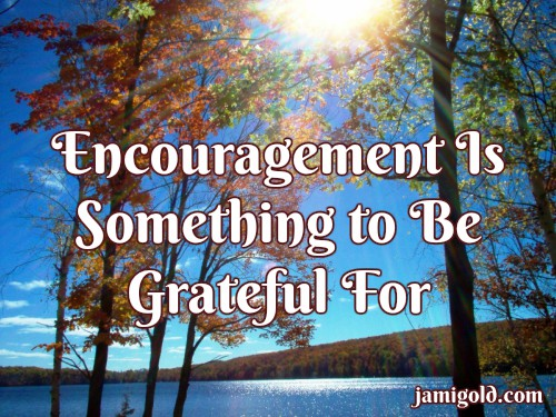 Sun rays over a lake and fall colors with text: Encouragement Is Something to Be Grateful For