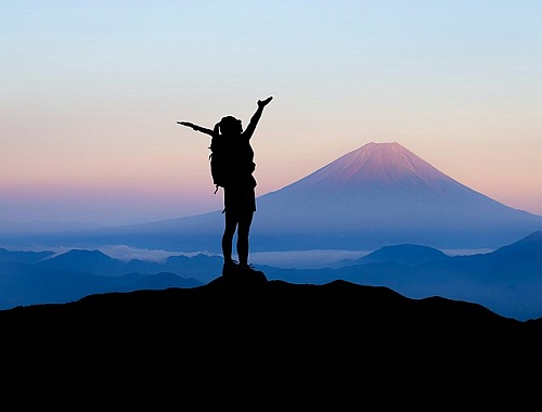 Hiker at top of mountain with arms uplifted