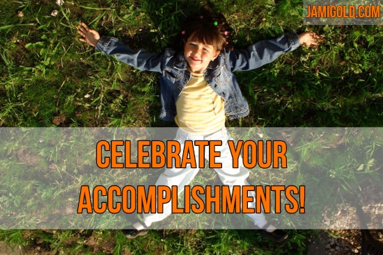 Overhead view of smiling girl on grass with arms spread out with text: Celebrate Your Accomplishments!