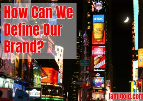 View of neon ads on Times Square at night with text: How Can We Define Our Brand?