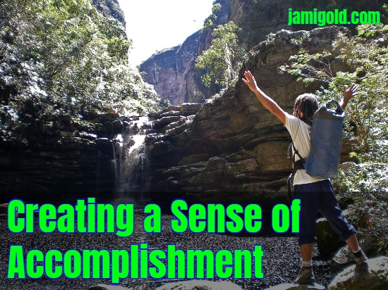 Man with arms upraised in front of waterfall with text: Creating a Sense of Accomplishment