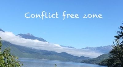 Peaceful lake and mountain landscape with text: Conflict free zone